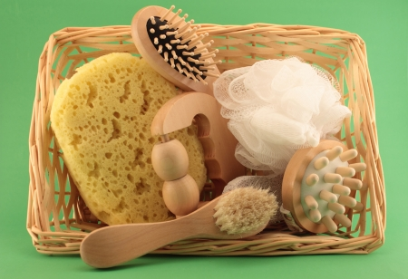 bristle: Elements for body care, grooming and hygiene in a spa basket on green background. Stock Photo