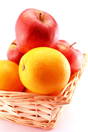 Oranges and apples in a basket. Close-up view. With white . Stock Photo