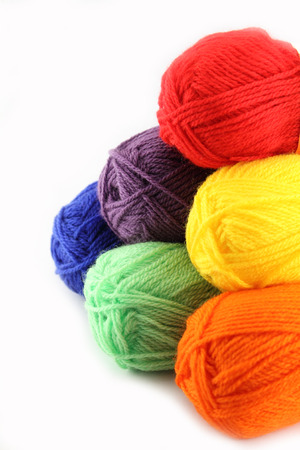 Six different colors of wool skeins isolated on white.