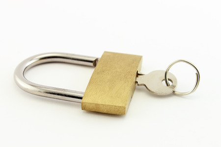 Onr key attached to a golden padlock. Isolated on a white background. photo