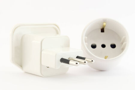 unplugged: Electric plug and socket unplugged on a white background.