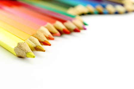 Composition with colored pencils on white background, closeup view
