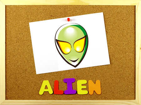 Written word ALIEN  in a corkboard with colorful letters  Illustration paper attached with a pin