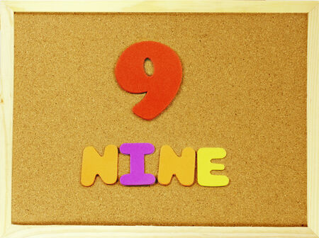 Corkboard with the word and number Nine written with colorful letters