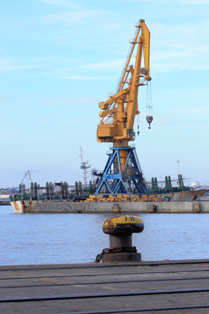 mooring bollards: View of the harbor, bay and a heavy crane for loading and unloading of containers in maritime vessels. Editorial