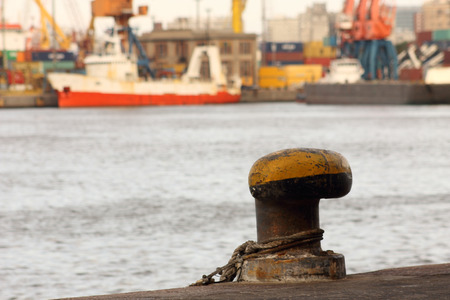 Close-up view of a bollard for mooring ships and bottom bay harbor, cranes and containers.