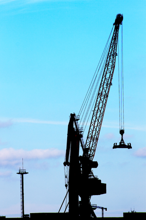 Silhouette of a crane against a blue sky. Conceptual image on trade and business. photo