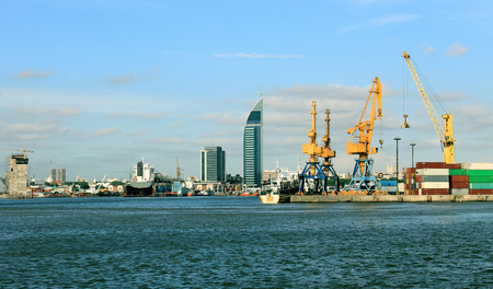 Coastal city view from the bay, including heavy cranes and containers for export of goods.