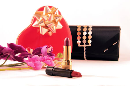 box of chocolates: Conceptual image. Metal box chocolates, red heart-shaped, two lipsticks and stylish black wallet women, isolated on white.