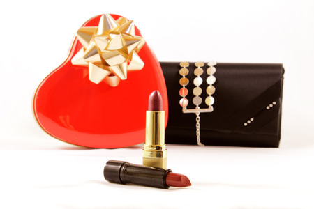 box of chocolates: Metal box chocolates, red heart-shaped, two lipsticks and stylish black wallet women, isolated on white.
