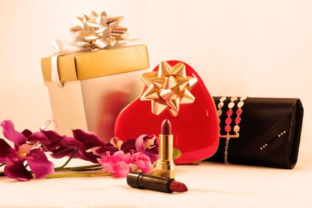 box of chocolates: Conceptual image with gifts for valentine. Metal box chocolates, red heart-shaped, two lipsticks and stylish black wallet women, isolated on white.
