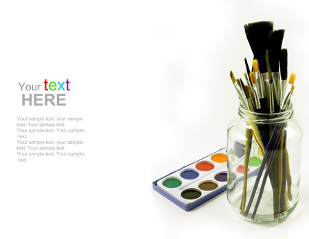 Watercolors and brushes in glass jar. Back to school concept. School stationery isolated over white with copyspace. photo
