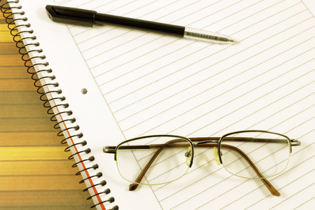 Notebook pen and eyeglasses. Back to school concept. photo