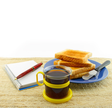 Notepad and pen on the breakfast table. With coffee and jam. photo