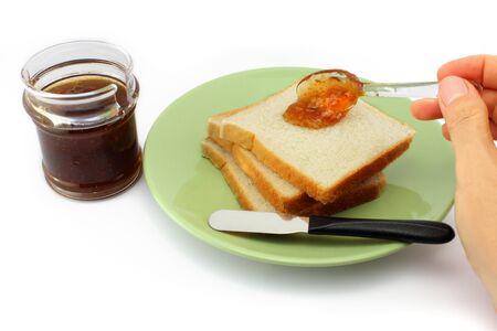 spreads: Hand spreads jam on fresh bread. Breakfast concept.