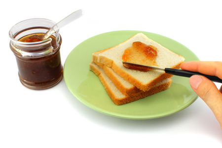 spreads: Hand spreads jam on fresh bread. Breakfast concept.