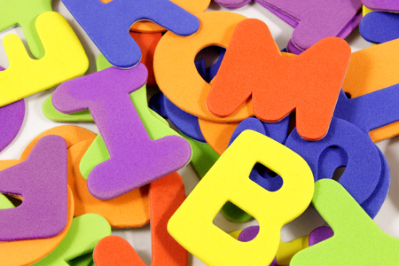 verbs: Close-up view of a background with scrambled letters in various colors.