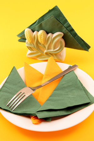 informal: Informal place setting with empty colorful plates, fork and paper napkins. Stock Photo