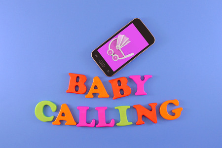 Cell phone with image of a baby stroller. Baby shower concept in flat lay with text Baby Calling