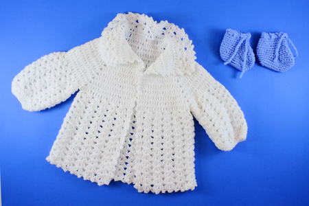 Hand-knit Organic Wool Baby Clothes. Baby shower concept in flat lay