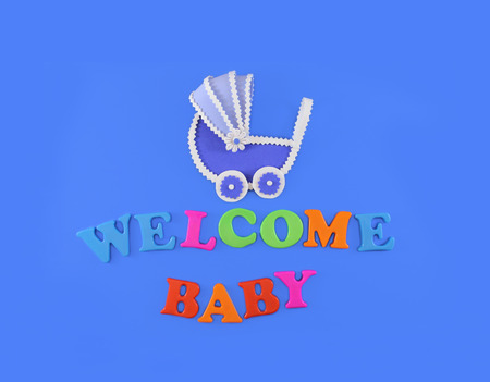 Baby carriage on light blue background, with text Welcome Baby. Baby shower concept in flat lay
