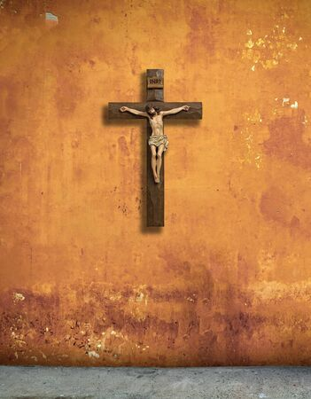 Catholic, christian cross on a shabby orange wall.