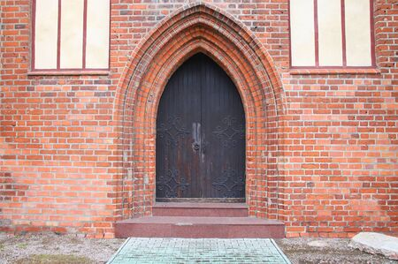 Medieval Gothic brick arch over a metal door