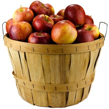 cesta de frutas: Manzanas sentado en una cesta de madera aisladas sobre fondo blanco.