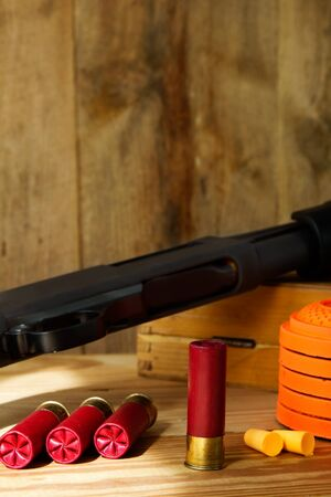 trap: Black 12 gauge pump action shotgun with shells, clay pigeons, and ear plugs sitting next to it. Stock Photo