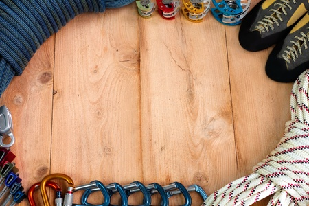 Rock climbing gear theme depicting a blue rock climbing dynamic rope, set of cams, climbing shoes, static rope, quickdraw carabiners, locking carabiners, set of climbing nuts, and a ATC belay device  photo