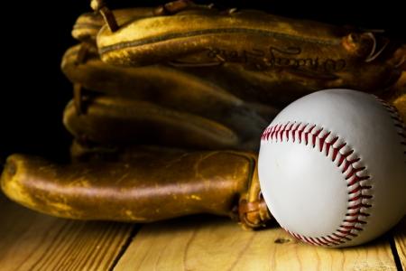 guante de beisbol: Béisbol sentado delante de un viejo guante de béisbol