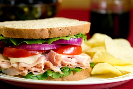 sandwiches:  A healthy fresh turkey sandwich with turkey, swiss cheese, lettuce, tomato and onions. Stock Photo