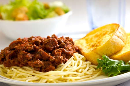 spaghetti dinner: Spaghetti with garlic bread sitting next to it with a salad and a glass of water in the background. Stock Photo