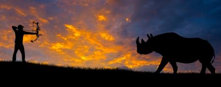 arco y flecha: Silueta de un cazador de arco apuntando a un rinoceronte contra una puesta de sol por la noche.