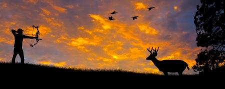cazador: Silueta de un cazador de arco apuntando a un ciervo de cola blanca contra una puesta de sol por la noche. Foto de archivo