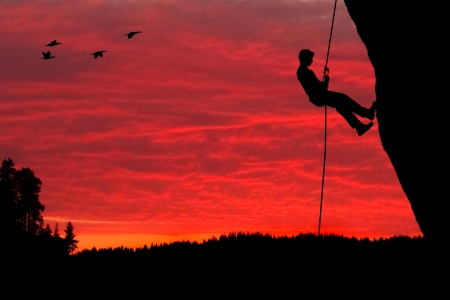 rappelling: Silhouette of a rock climber rappelling down a cliff against an evening sunset