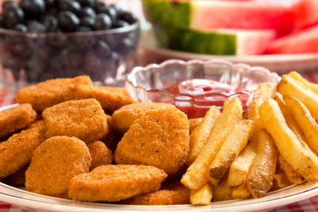 nuggets: Chicken nuggets and french fries with watermelon and blueberries in the background.