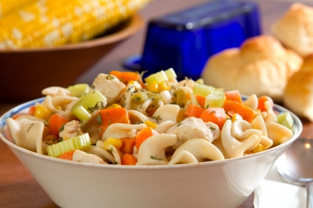 supper: Chicken Noodle Soup with corn, butter and bread in the background.  Stock Photo