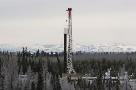drilling well: Drillng rig working in the Alberta foothills Stock Photo