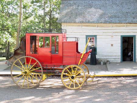 Old wagon parked beside wooden sidewalk. Stock Photo