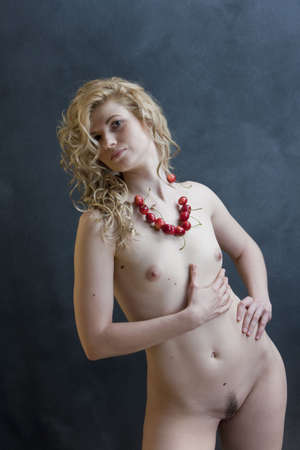 Young sexual model. Photographing in studio. Beads from a sweet cherry.