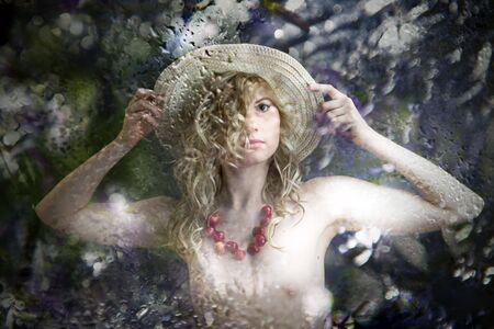 Young sexual model. Photographing in studio. Beads from a sweet cherry and Straw hat. Stock Photo - 7146604
