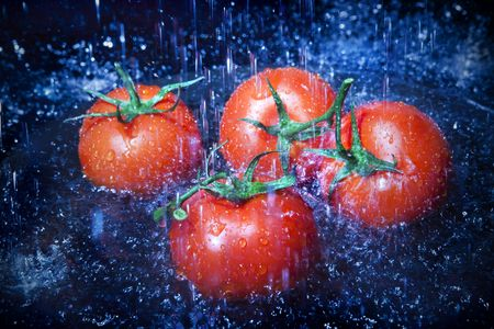 Fresh tomatoes under running tap with water drops photo