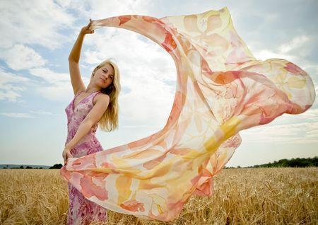 Mooie vrouw met vliegende sjaal op gouden gebied.  Stockfoto
