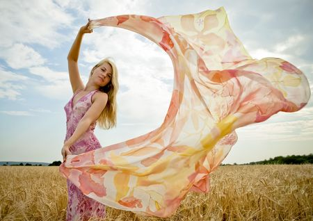 Pretty woman with flying shawl in golden field.  Stock Photo