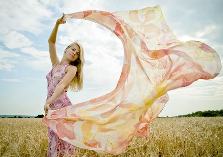 Pretty woman with flying shawl in golden field.