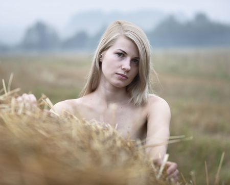 Young sexy woman on a summer day among the straw. photo