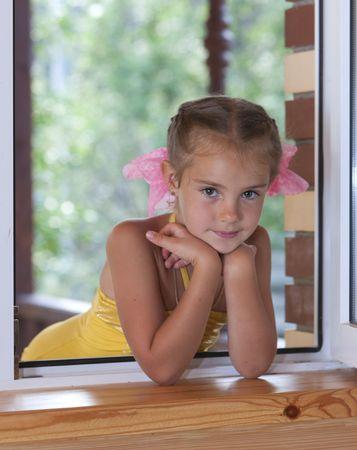 Een portret van een zes-jarige meisje in het venster in de middag.