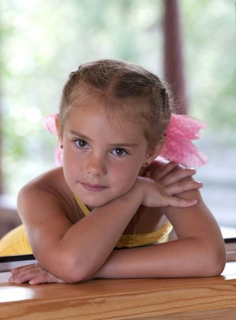 A portrait of a six-year girl  in the window in the afternoon. photo