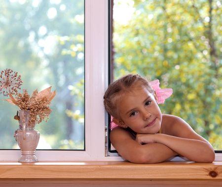 one teenage girl only: Un retrato de una ni�a de seis a�os en la ventana en la tarde.